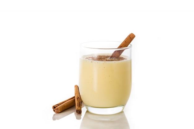 Zabaione casalingo con cannella in vetro isolato su bianco. dolce tipico natalizio. copyspace