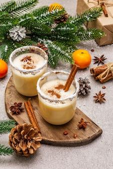 Zabaione con cannella e noce moscata per natale e vacanze invernali. bevanda fatta in casa in bicchieri con bordo speziato. mandarini, candele, regali.