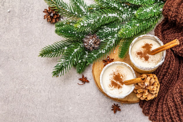 Zabaione fatto in casa con cannella in vetro. dolce tipico natalizio. brunch sempreverde di abete, coni, plaid accogliente, neve artificiale.