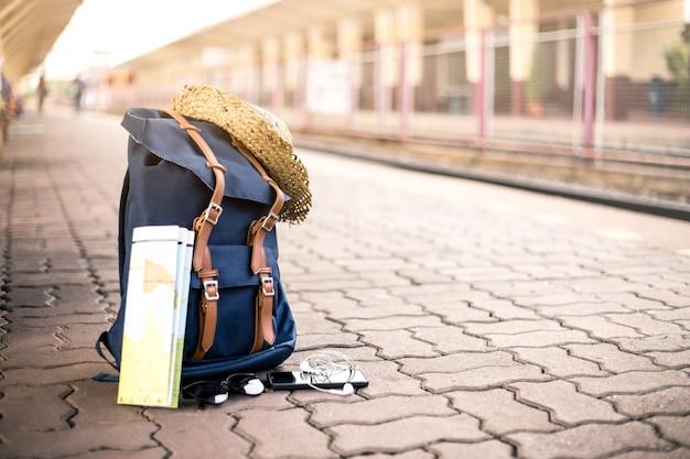 Zaino con cappello, mappa, occhiali da sole, auricolare e smartphone nella stazione ferroviaria