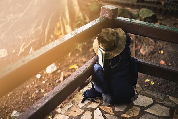Zaino con mappa e cappello sul pavimento