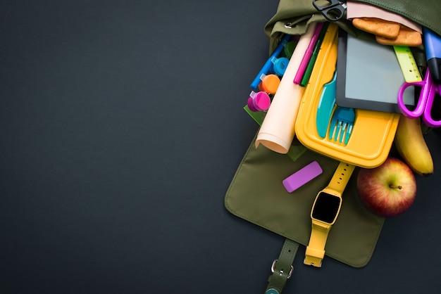 Zaino con materiale scolastico su sfondo nero.