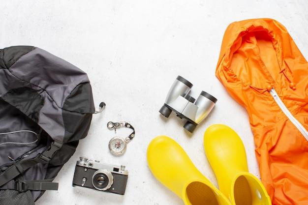 Zaino da viaggio, bussola, stivali di gomma, giacca, macchina fotografica e binocolo su uno sfondo bianco. concetto di escursionismo, turismo, campo, montagne, foresta.