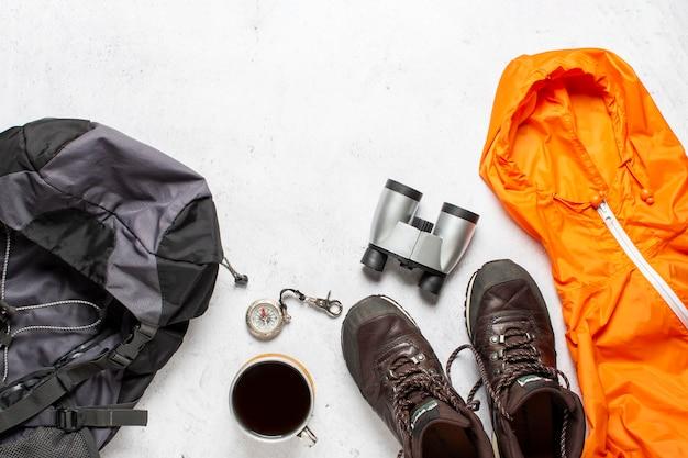 Zaino da viaggio, bussola, stivali, giacca, macchina fotografica e binocolo su uno sfondo bianco. escursione di concetto, turismo, campo.