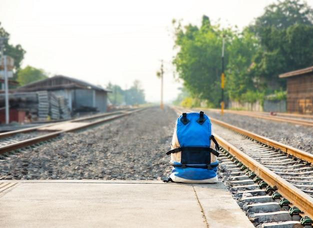 Zaino da viaggio sul terreno della stazione ferroviaria. concetto di viaggio e zaino.