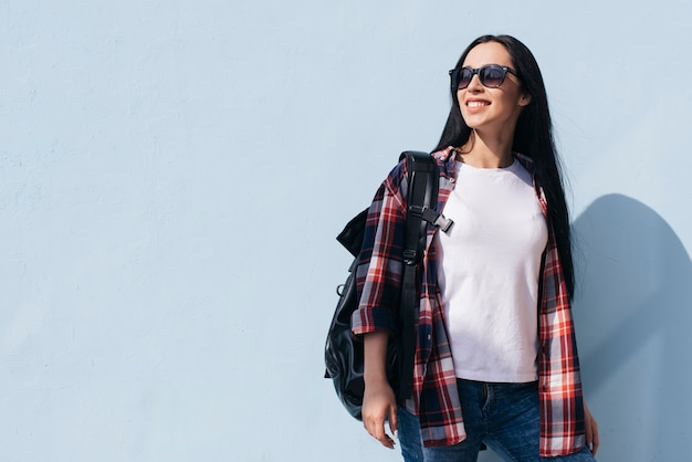 Zaino di trasporto della donna alla moda che posa contro la parete blu