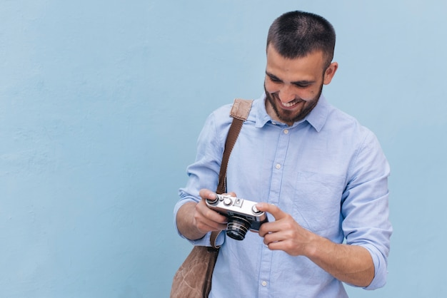 Zaino di trasporto sorridente del giovane ed esaminare macchina fotografica che sta vicino alla parete blu