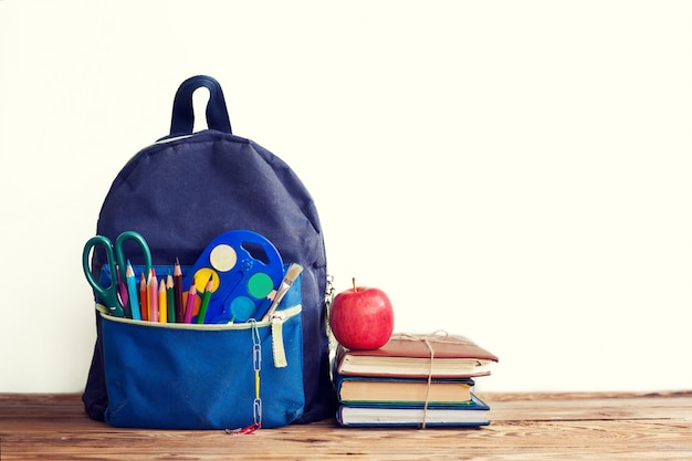 Zaino full school con libri e mela su bianco.
