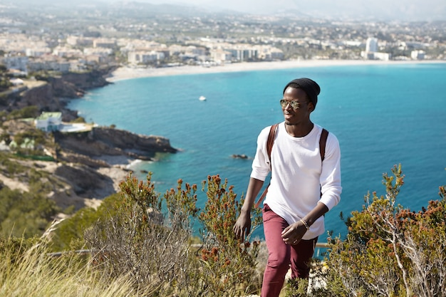 Zaino in spalla attraente con la pelle scura vestito casual che viaggia in città europea, tornando dalla piattaforma panoramica