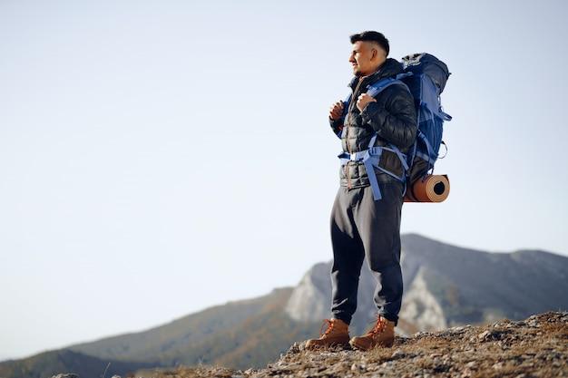 Zaino in spalla maschio in attrezzatura escursionistica in piedi in cima alla montagna