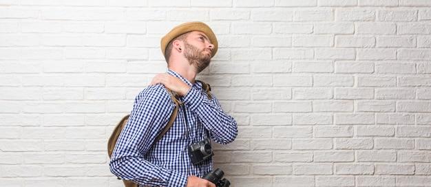 Zaino indossando uomo giovane viaggiatore e una macchina fotografica d'epoca con dolore alla schiena a causa di stress da lavoro