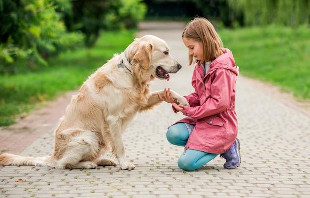 Zampa del cane della holding della bambina sulla strada asfaltata nel parco