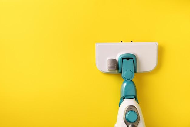 Zazzera del pulitore del vapore su fondo giallo.