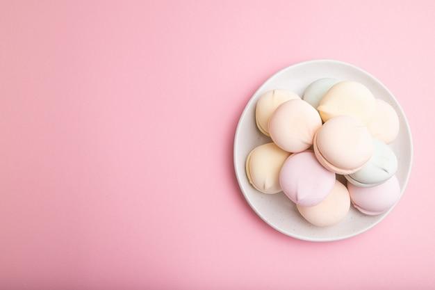 Zefiro colorato o marshmallow su sfondo rosa pastello.