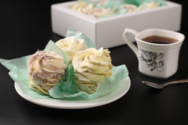 Zefiro fatto in casa, caramelle gommosa e molle in una scatola e tazza di caffè su una superficie scura, orientamento orizzontale