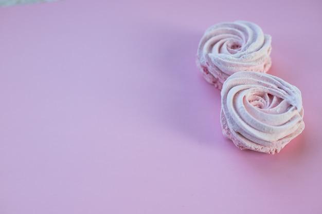 Zefiro o caramella gommosa e molle casalingo rosa sulla parete rosa. marshmallow, meringa, zephyr. concetto di torte di caramelle. zefiro, soufflé, meringa fatta in casa