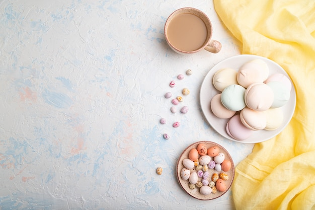Zefiro o caramella gommosa e molle colorato con la tazza di caffè e confetti su fondo concreto bianco.