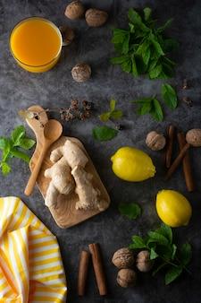 Zenzero, limoni e foglie di menta su superficie scura,