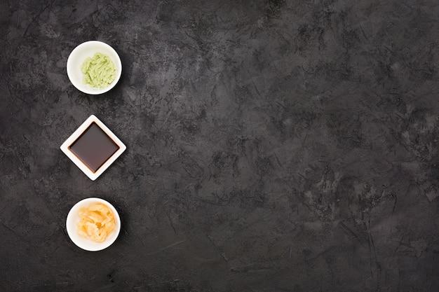 Zenzero marinato; salsa di soia e scodella wasabi disposte in fila sulla superficie nera strutturata