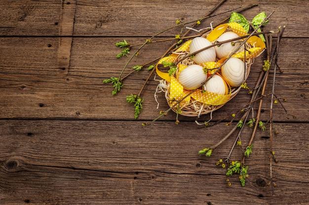 Zero rifiuti concetto di pasqua. ramoscelli di primavera con foglie verdi fresche, uova in legno nel cestino, nastro a pois