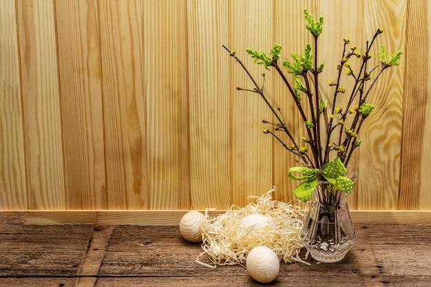 Zero rifiuti concetto di pasqua. ramoscelli di primavera con foglie verdi fresche. vaso di vetro, uova di legno, nido, nastro a pois.
