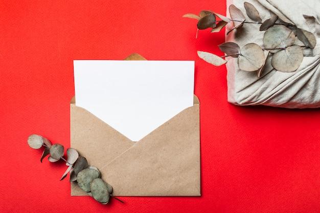 Zero rifiuti concetto di san valentino sul rosso. confezione regalo ecologica in stile furoshiki, busta in carta artigianale, cartolina d'auguri vuota. vista dall'alto verso il basso o disteso. copia spazio per il design