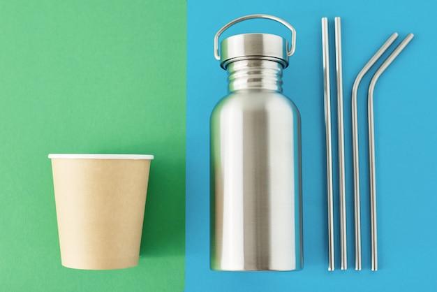 Zero rifiuti concetto eco-friendly. riutilizzabili articoli in plastica gratis su uno sfondo colorato di blu e verde. vista dall'alto della bottiglia di alluminio, tubi di metallo e tazza di caffè di carta