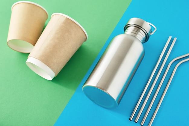 Zero rifiuti concetto eco-friendly. riutilizzabili articoli in plastica gratis su uno sfondo colorato di blu e verde. vista dall'alto della bottiglia di alluminio, tubi di metallo e tazze di caffè di carta