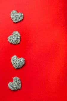 Zero rifiuti, concetto ecologico di san valentino. cuori con filato su sfondo rosso. copia spazio per testo o design. vista dall'alto o disteso