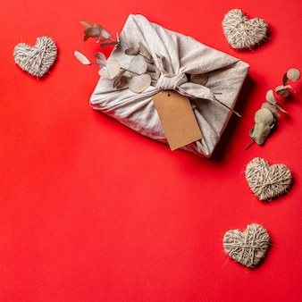 Zero rifiuti, confezione regalo ecologica di san valentino in stile furoshiki con eucalipto secco ed etichetta artigianale vuota.