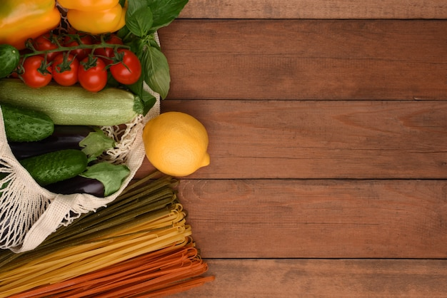 Zero sprechi. borsa a rete con verdure e spaghetti vegetali su fondo in legno con copia spazio. eco bag con verdure fresche e limone.