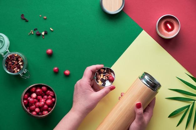 Zero sprechi di tè nella borraccia da viaggio. preparare un'infusione di erbe in una fiaschetta di bambù isolata ecologica con miscela di erbe e bacche di mirtillo fresco. piatto alla moda con mani, carta verde rossa e gialla.