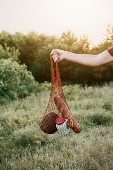 Zero sprechi, niente plastica, stile di vita ecologico. mano maschile con borsa in rete di cotone riutilizzabile rustica
