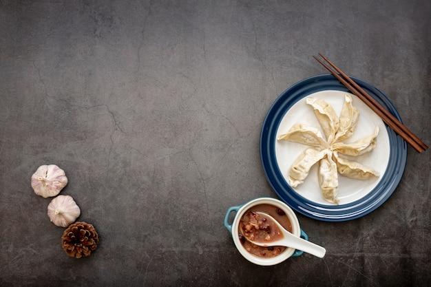 Zolla bianca con dim sum ed aglio su una priorità bassa grigia