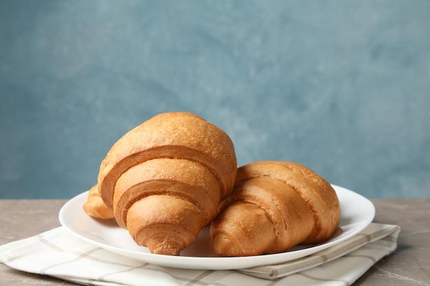 Zolla con i croissant sulla tabella grigia, spazio per testo