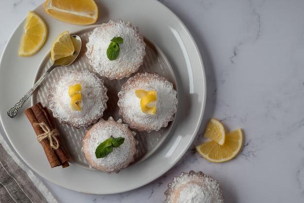 Zolla con i muffin saporiti del limone sulla tabella di marmo, vista superiore. spazio per il testo