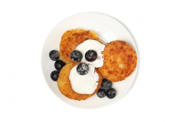 Zolla con i pancake del formaggio isolati su superficie bianca