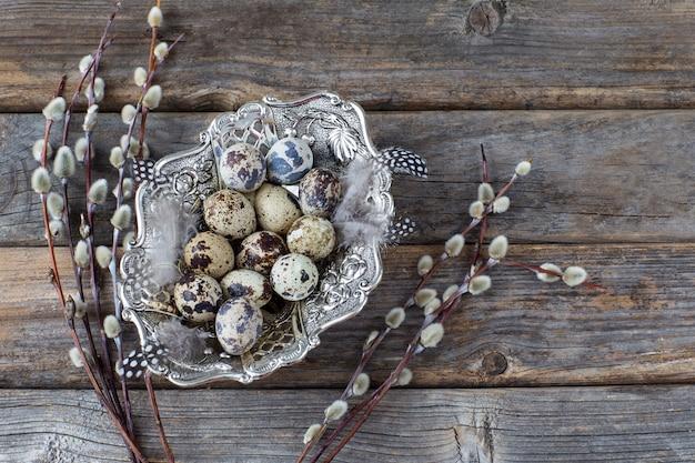 Zolla d'argento con le uova di quaglia e salice su fondo di legno - fondo di pasqua