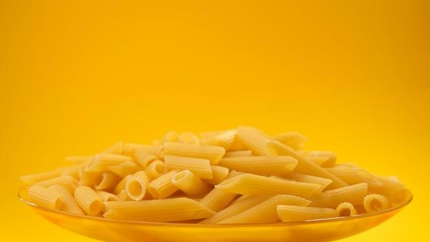 Zolla della pasta italiana grezza del rigne del penne su colore giallo con lo spazio della copia