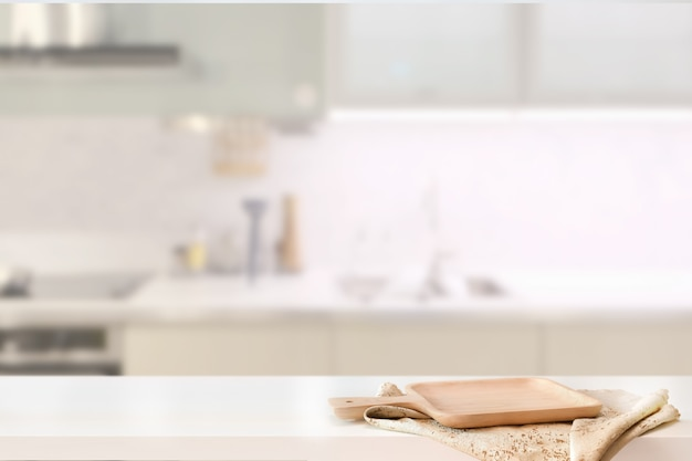 Zolla di legno sulla tabella bianca nella priorità bassa della stanza della cucina e spce della copia