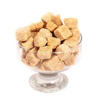 Zolletta di zucchero di canna marrone in vaso di vetro