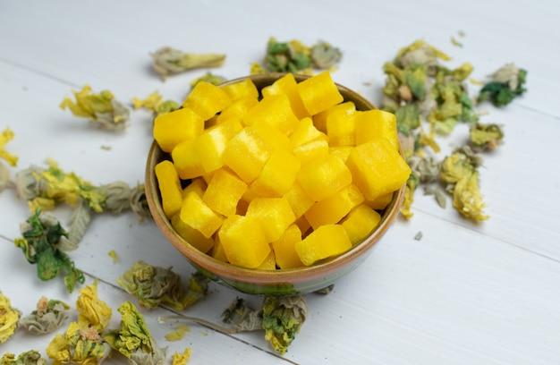 Zollette di zucchero di frutta in una ciotola con erbe secche su superficie di legno bianco.