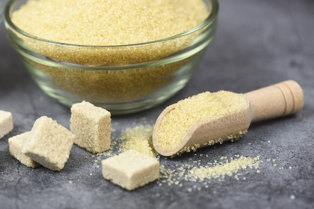 Zollette di zucchero e mucchio di zucchero bruno sulla ciotola e mestolo di legno sul tavolo