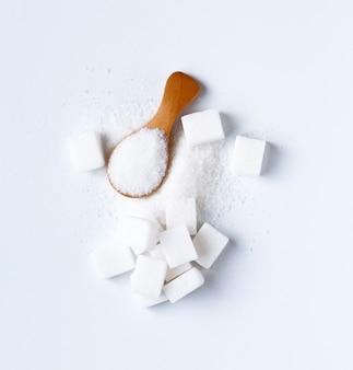 Zollette di zucchero e zucchero nel cucchiaio. zucchero bianco su sfondo bianco. zucchero diverso