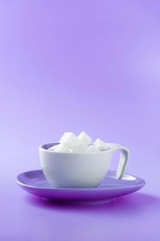 Zollette di zucchero in una tazza di caffè con superficie viola