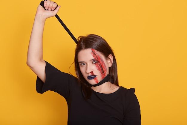 Zombie morta femmina pronta per la festa di halloween, indossa un abito nero e un trucco spaventoso, soffocandosi con la pace della stoffa