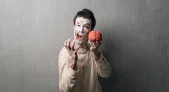 Zombie Terrorizzato che mangia un cervello. Vacanze di Halloween