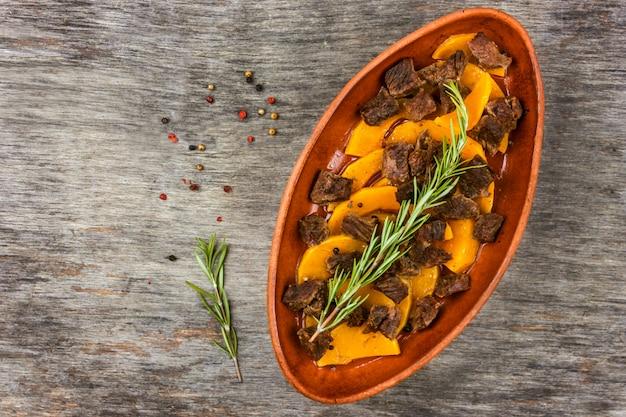Zucca affettata al forno con carne in un vaso di argilla. pasto autunnale con rosmarino e spezie