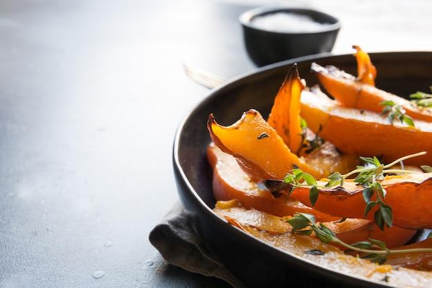 Zucca affettata arrostita con timo e sale. cibo vegano sano.