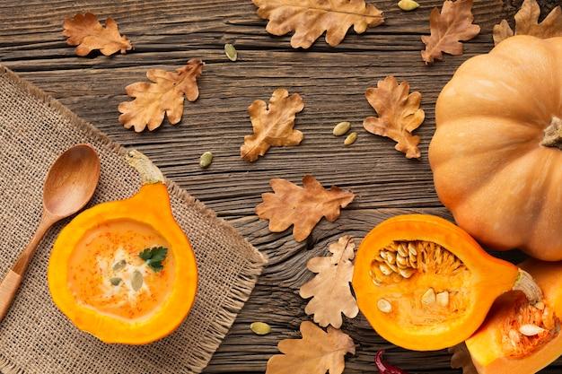 Zucca affettata piana e cucchiaio di legno con le foglie